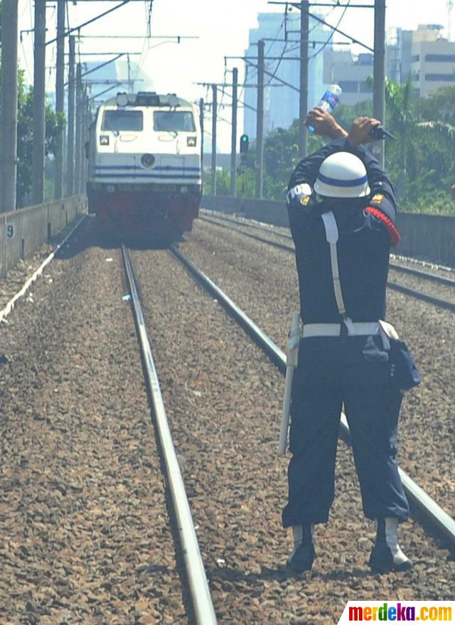 Petugas keamanan menghentikan kereta saat kebakaran di kolong jalan rel Cikini di Jalan Proklamasi, Jakarta, Minggu (27/5).