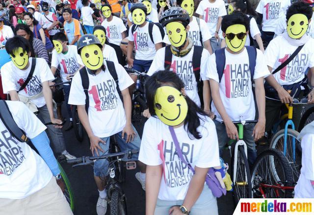 Sejumlah komunitas sepeda mengenakan topeng memakai kaos bertuliskan '1 hari tanpa mengeluh' di Bundaran HI Jakarta, Minggu (27/05).
